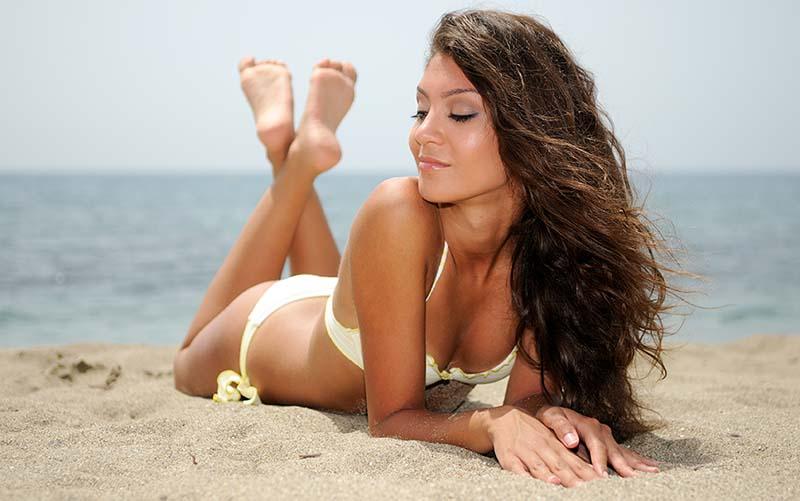 ragazza al sole,abbronzatura,tintarella in spiaggia
